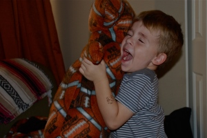 boy hugging stuffed pillow