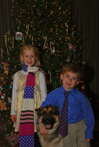 girl and boy with german shepard in front of christmas tree