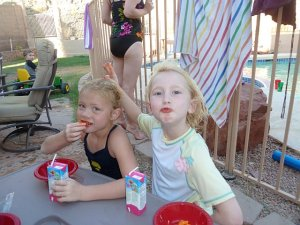 two young girls by pool eating cheetos drinking juice box
